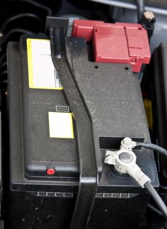 Accumulator (storage battery) under an open bonnet of a car