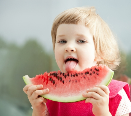 Funny little girl eating big slice of watermelon photo