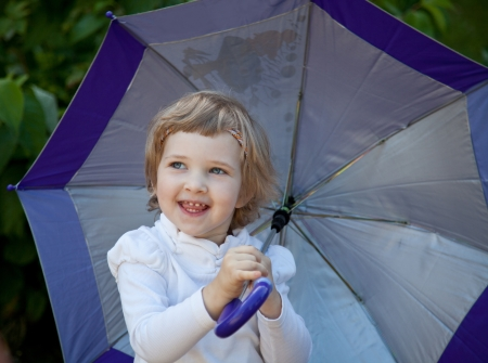 positiveness: Happy laughing little girl with umbrella in a summer park