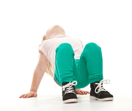 Little girl doing sport exercises on white background photo