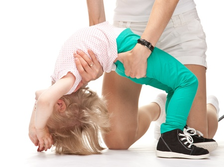 Mother helping her little daughter to do gymnastics, white background photo