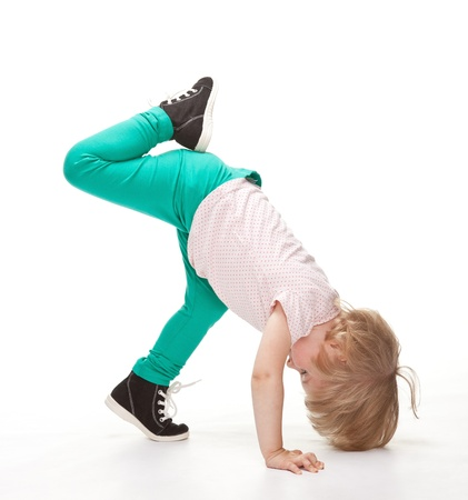 Active little girl doing sport exercises on white background