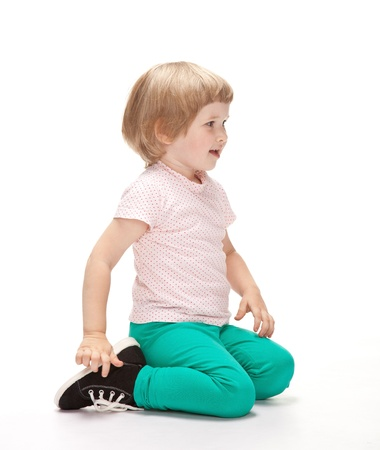 Happy little girl sitting on the floor on white background photo