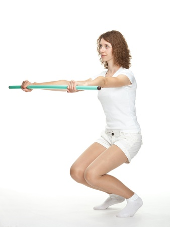 Sporty girl squatting on white background photo