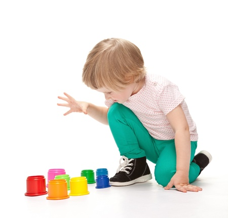 Cute little girl playing with toys sitting on the floor on white background photo