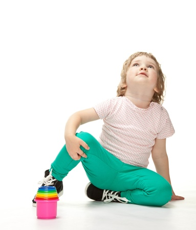Cute little girl sitting on the floor on white background Stock Photo