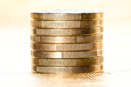 Stacked coins - column of euro coins on golden background photo