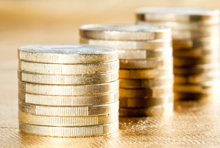 Stacked coins - three columns of euro coins on golden background photo
