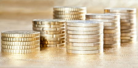 Stacked coins - side view of many columns of euro coins on golden background photo