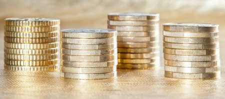 Stacked coins - side view of several columns of euro coins on golden background photo