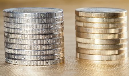 Stacked coins - two columns of euro coins on golden background photo