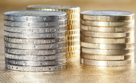Stacked coins - columns of euro coins on golden background photo