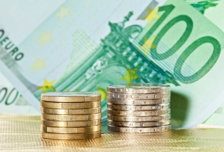 Stacked coins and euro banknotes on golden background photo