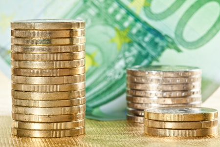 Stacked coins and euro banknote on golden background photo