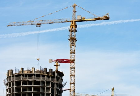 Tower crane and reinforced building under construction; project site against blue sky photo