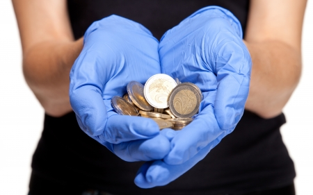 Human hands in medical gloves holding coins  on white background photo
