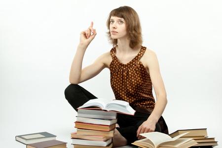 diligente: Hermosa joven estudiante estudiando sentada en el suelo, el fondo blanco
