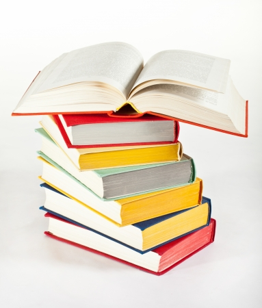 Multicolored stacked books on neutral background