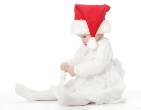 first miracle: Cute baby girl in Santas hat playing on the floor Stock Photo