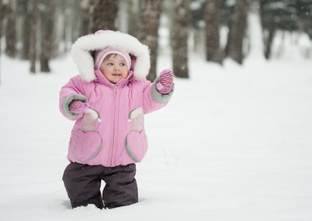 Adorable little baby playing in a snowy winter park photo