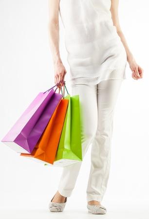 chicas de compras: Ni�a de la celebraci�n multicolores bolsas de papel - tiro del primer en el fondo blanco