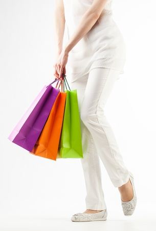 Girl holding multicolored shopping paper bags - closeup shot on white background Stock Photo - 16235104