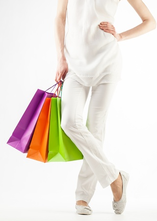Girl holding multicolored shopping paper bags - closeup shot on white background Stock Photo - 16235115