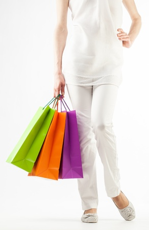 Girl holding multicolored shopping paper bags - closeup shot on white background Stock Photo - 16235114