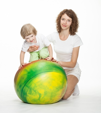 Happy mother doing sport exercises with little daughter; white background photo
