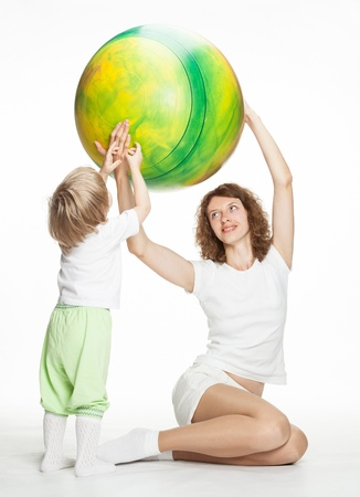 limbering: Happy mother doing sport exercises with little daughter; white background