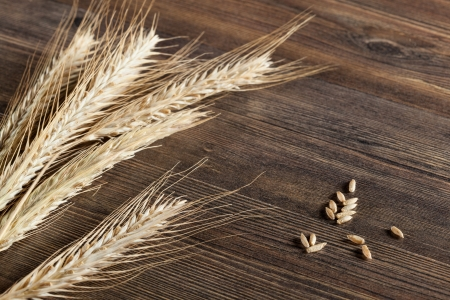 Wheat ears on wooden table photo