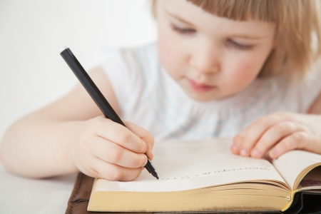 recitation: Attentive little girl writing letters with a pen; white background