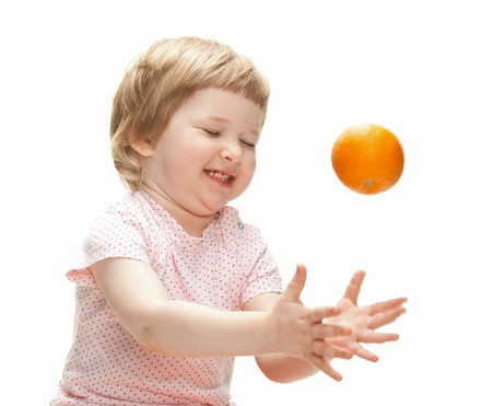 Happy laughing child playing with orange, white background Stock Photo - 16948727
