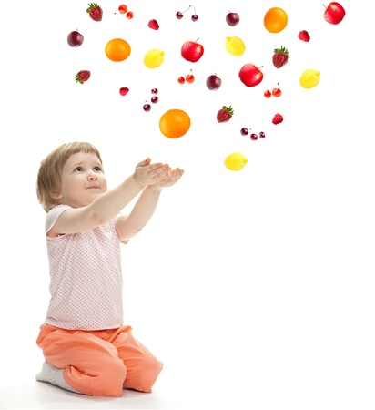 Little girl reaching her hands out and catching fruits, isolated on white photo