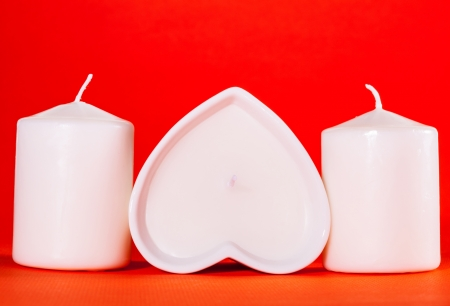 White candles for Valentines day on red background photo
