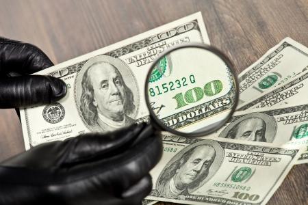 vals geld: Honderd dollar biljetten onder een vergrootglas worden geïnspecteerd door de mens in zwarte handschoenen Stockfoto