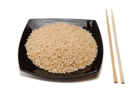 Rice in bowl and chopsticks isolated on white photo