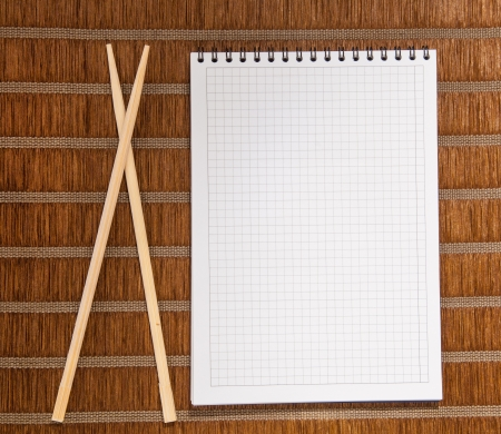 Squared paper loose-leaf note sheet and chopsticks photo