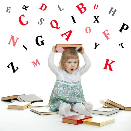 Scared little child sitting on the floor surrounded by books and alphabetical letters photo