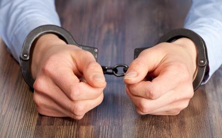 Handen in handboeien op de tafel Stockfoto