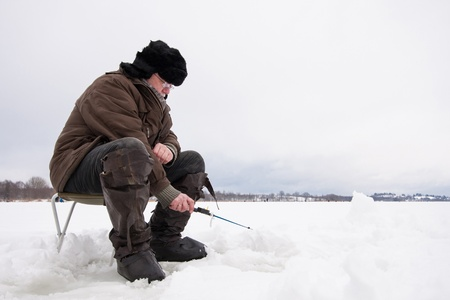 Russian fisherman in earflapped fur hat and boots at winter fishing Stock Photo - 17850852