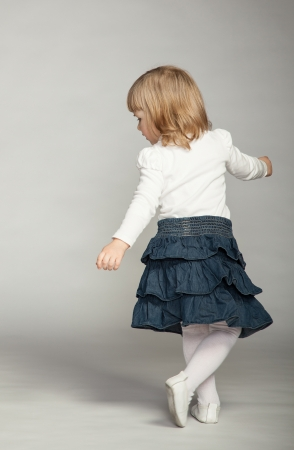 Playful baby girl dancing; full length studio portrait on dark background photo