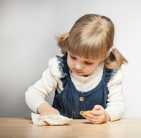 Little girl puts things in order with duster in her room, grey background