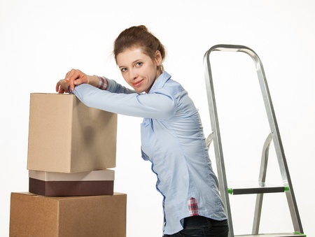 Smiling young woman near a pile of boxes on white background photo