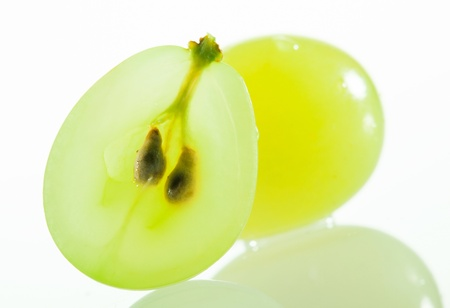 Juicy green grapes - macro shot of cut berries on white background Stock Photo