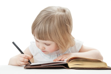 little table: Attentive little girl writing letters with a pen; white background