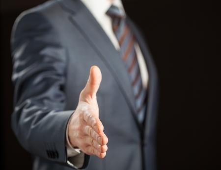 Businessman offering handshake to you on black background