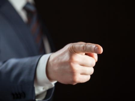 Businessman pointing forward on dark background