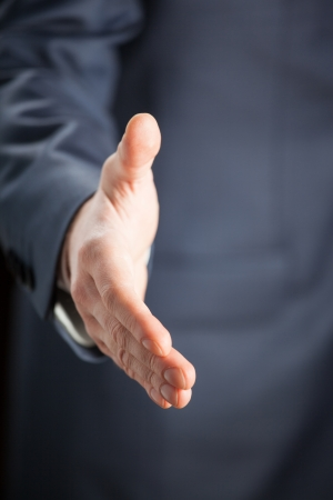 Businessman offering handshake to you - closeup shot Stock Photo