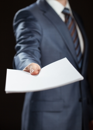 Businessman reaching out documents to you on black background photo